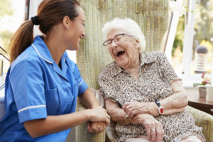 Caregiver laughing with senior client