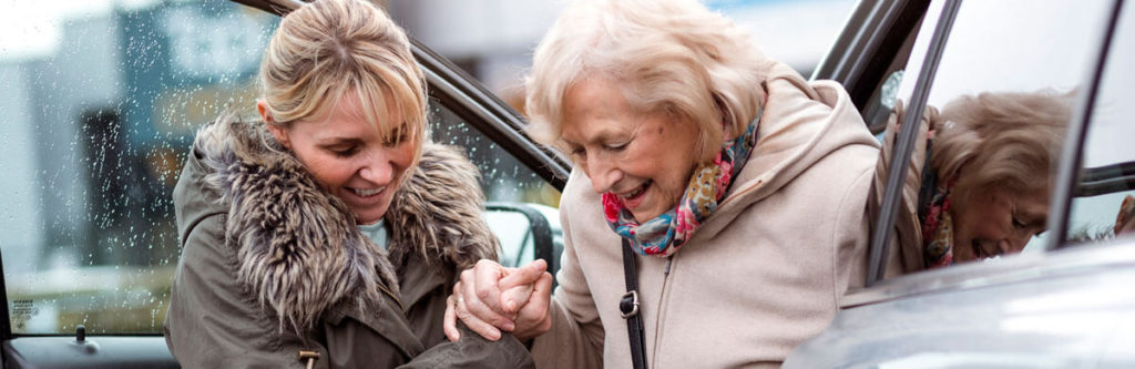 caregiver assisting client out of a car